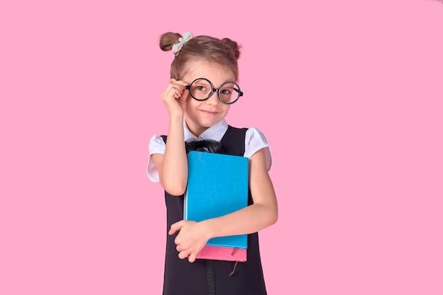 Schattig klein meisje met een bril en boeken over roze ruimte, ruimte voor tekst. concept lezen