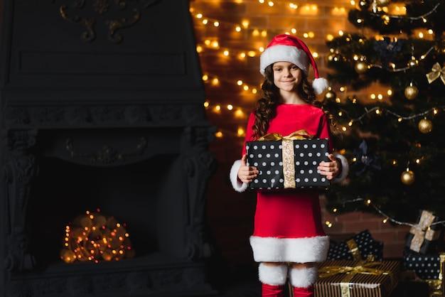 Schattig klein meisje met een geschenk in de buurt van de kerstboom in een rood kerstkostuum