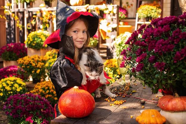 Schattig klein meisje met een halloween-kostuum dat plezier heeft op een pompoenpleister op een mooie herfstdag