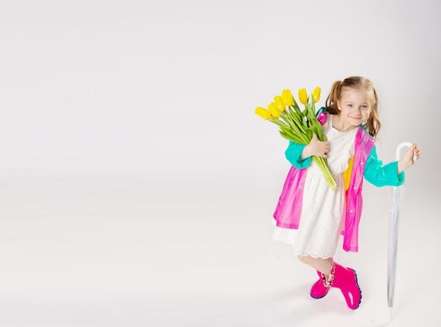 Schattig klein meisje met een heldere regenjas en een paraplu met bloemen