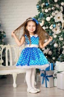 Schattig klein meisje met een kerstcadeau, in een blauwe jurk naast versierde kerstbomen.