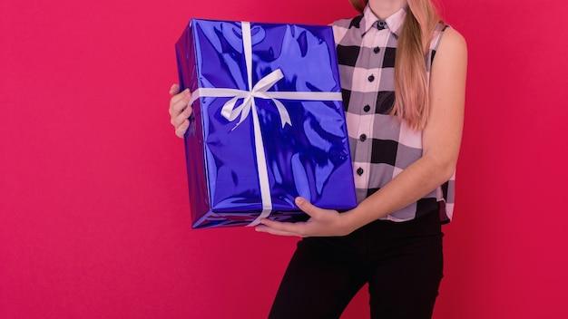 Schattig klein meisje met een kerstmuts die geïsoleerd staat op een rode achtergrond, met de huidige doos