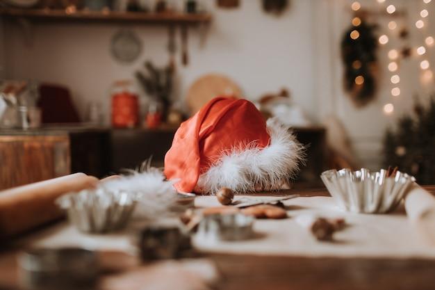 Schattig klein meisje met een kerstmuts is aan het dollen aan de kersttafel winter nieuwjaarskeuken