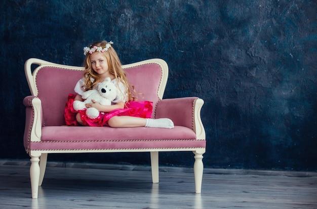 Schattig klein meisje met een krans op haar hoofd zittend op een roze bank met een witte teddybeer tegen de donkere muur.
