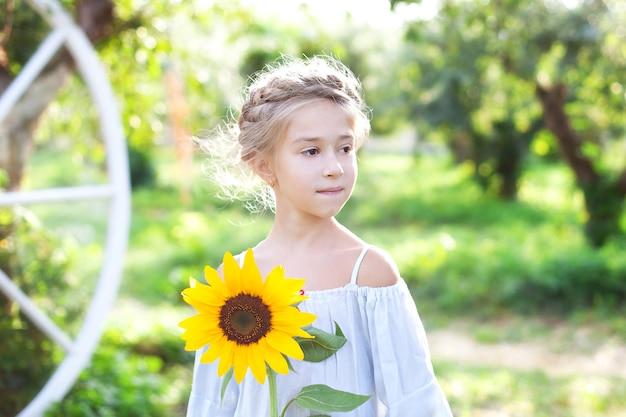 Schattig klein meisje met een staartje op haar hoofd houdt een zonnebloemkind met een zonnebloem in de tuin