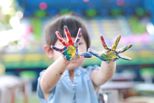 Schattig klein meisje met geschilderde handen, selectieve aandacht aan kant