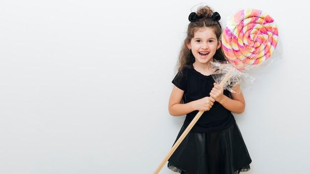 Schattig klein meisje met gigantische lolly en kopie ruimte