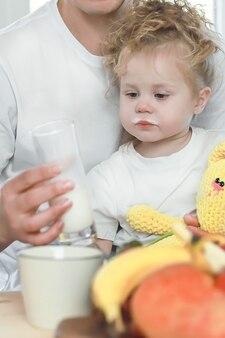 Schattig klein meisje met haar vader die melk drinkt over raamachtergrond gelukkig familieconcept