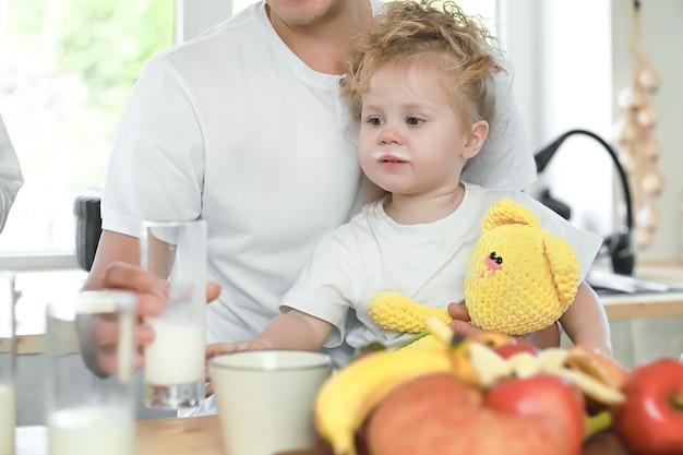Schattig klein meisje met haar vader die melk drinkt over raamachtergrond vitamine-ontbijt in de keuken