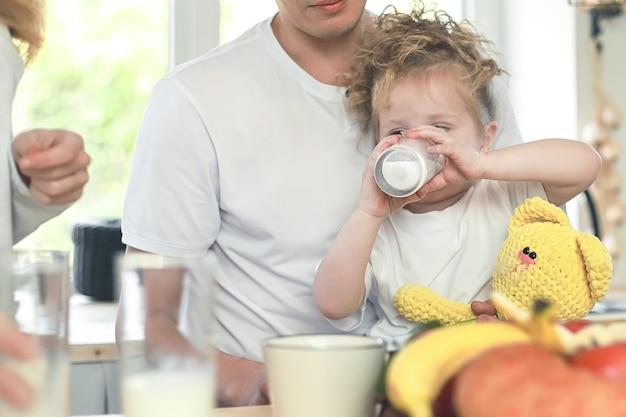 Schattig klein meisje met haar vader melk drinken over raam achtergrond ontbijt in lichte keuken