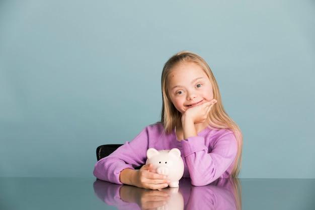 Schattig klein meisje met het syndroom van down geld besparen in een spaarvarken