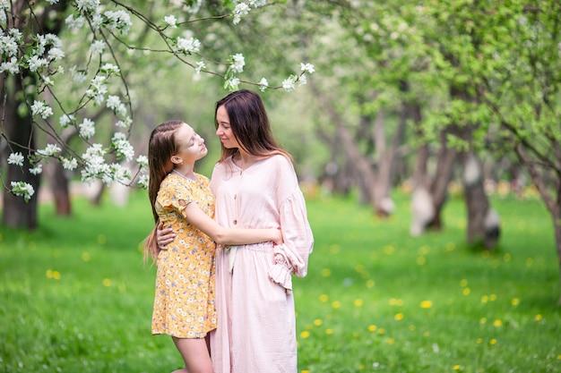 Schattig klein meisje met jonge moeder in bloeiende kersentuin op mooie lentedag