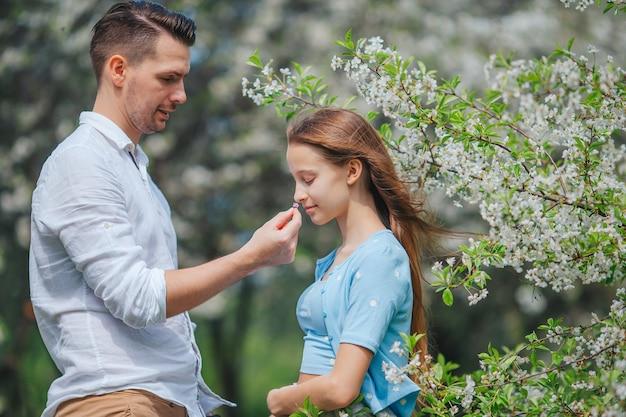 Schattig klein meisje met jonge vader in bloeiende kersentuin op mooie lentedag