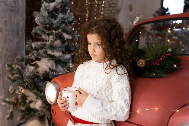 Schattig klein meisje met kerst kopje tee in de buurt van rode auto en kerstbomen met verlichting.
