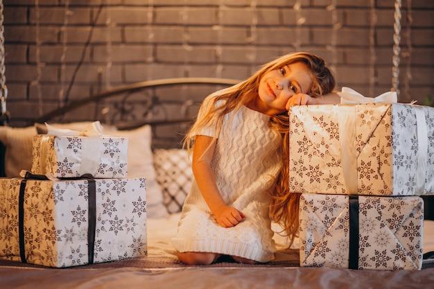 Schattig klein meisje met kerstcadeaus in bed