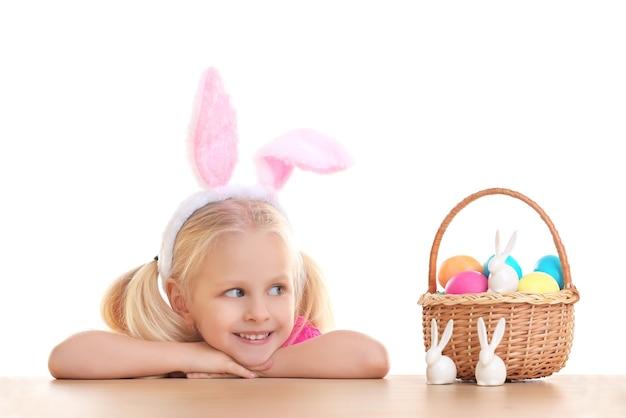Schattig klein meisje met konijnenoren en mand vol paaseieren op witte achtergrond