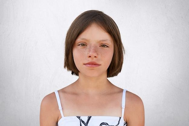 Schattig klein meisje met kort donker geknipt haar, bruine brede glanzende ogen, dunne lippen en sproeten huid in witte zomerjurk camera kijken met serieuze blik geïsoleerd op witte betonnen muur