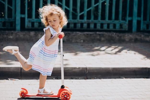 Schattig klein meisje met krullend park rijden scooter