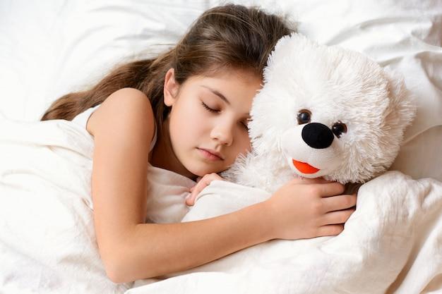 Schattig klein meisje met lang haar slapen met teddybeer in bed