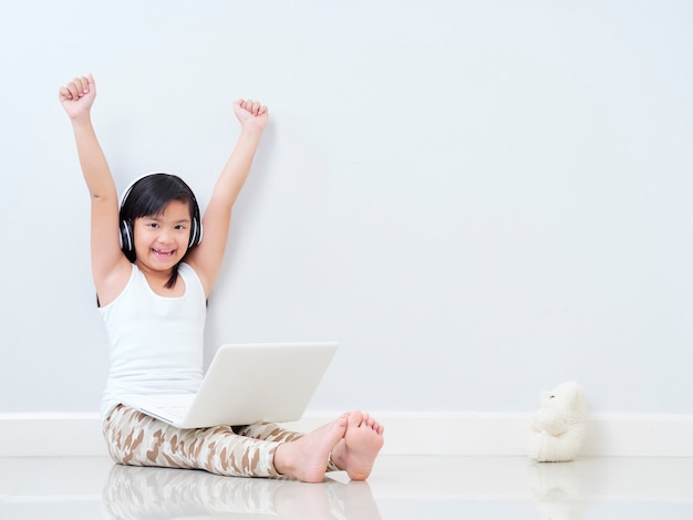 Schattig klein meisje met laptop thuis