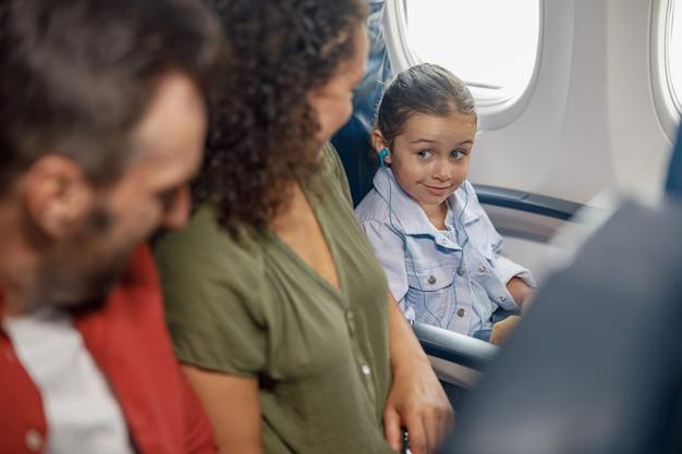 Schattig klein meisje met oortelefoons terwijl ze in het vliegtuig zit, naar muziek luistert, naar haar ouders kijkt, samen met familie reist. reizen, vakantie concept