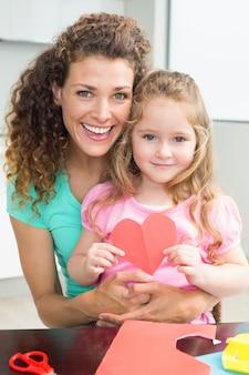 Schattig klein meisje met papieren hart zittend op moeders schoot