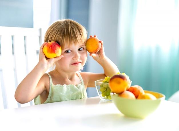 Schattig klein meisje met perziken in handen aan de tafel