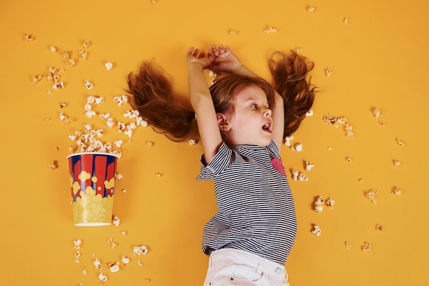 Schattig klein meisje met popcorn liggend op de gele vloer.