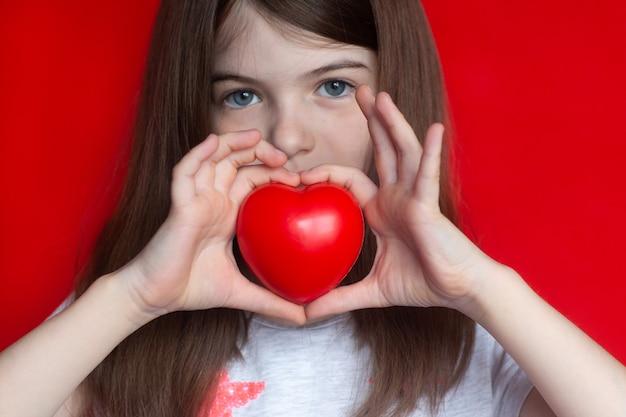 Schattig klein meisje met rood hart, concepten van liefde, kindertijd, hulp en medisch