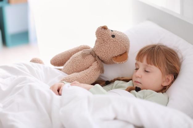 Schattig klein meisje met speelgoed beer slapen in bed