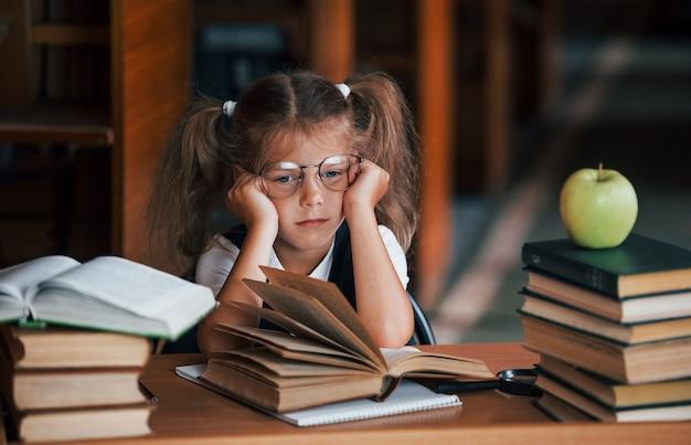 Schattig klein meisje met staartjes is in de bibliotheek