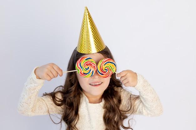 Schattig klein meisje met twee grote lollies op haar ogen in een feestelijke hoed op een witte geïsoleerde achtergrond met een streamer. ruimte voor tekst. klein meisje viert verjaardag, concept vakantie