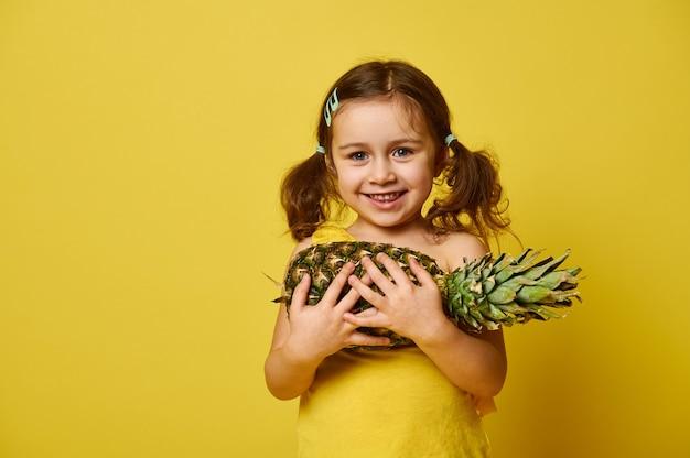Schattig klein meisje met twee paardenstaarten, gekleed in geel, met een ananas en schattig glimlachend, poseren voor de camera op een geel met kopie ruimte