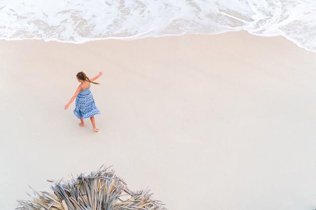 Schattig klein meisje met veel plezier in ondiep water. uitzicht van bovenaf op een verlaten strand met turquoise water