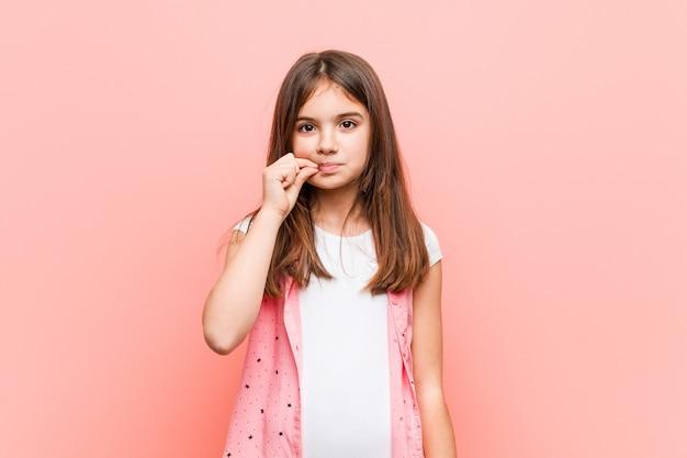 Schattig klein meisje met vingers op de lippen houden een geheim.