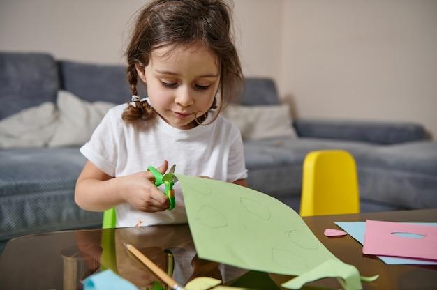 Schattig klein meisje met vlechten zittend aan tafel en gericht op het snijden van vormen uit kleur groen papier.