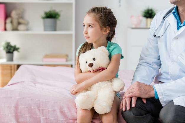 Schattig klein meisje met witte teddybeer kijkt door raam zittend op bed naast arts in whitecoat