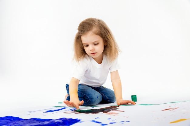Schattig klein meisje, modern kapsel, wit shirt, spijkerbroek tekent foto's met haar handen met verf. isoleren.