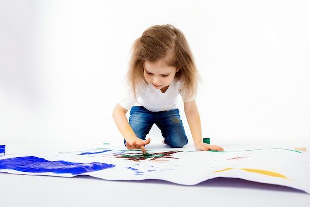 Schattig klein meisje, modern kapsel, wit shirt, spijkerbroek tekent foto's met haar handen met verf