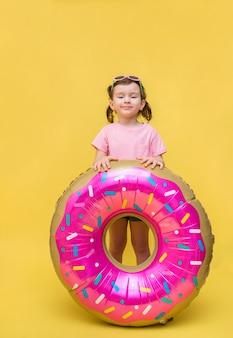 Schattig klein meisje op een gele ruimte. meisje met bril en een ballon in de vorm van een donut. een meisje in een roze t-shirt met een roze donut
