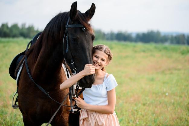 Schattig klein meisje op een paard in een zomer veld jurk. zonnige dag