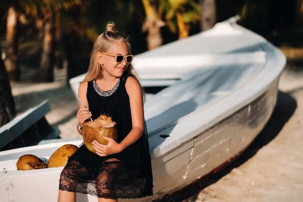 Schattig klein meisje op het strand met kokos terwijl u ontspant. een meisje op het strand in de buurt van een boot met een kokosnoot. mauritius eiland.