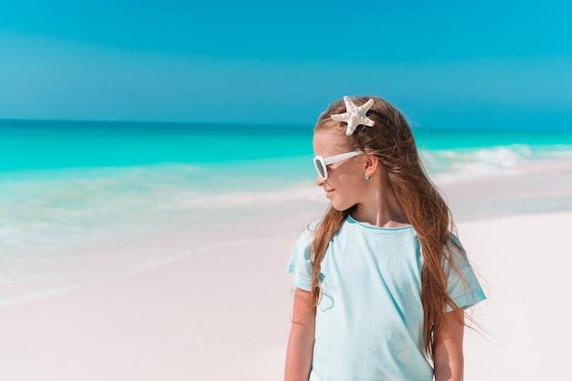 Schattig klein meisje op het strand tijdens de zomervakantie