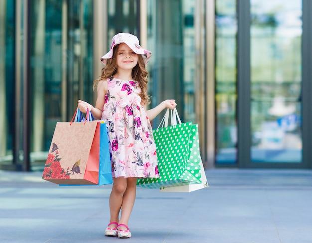 Schattig klein meisje op winkelen, portret van een kind met boodschappentassen, winkelen, meisje.