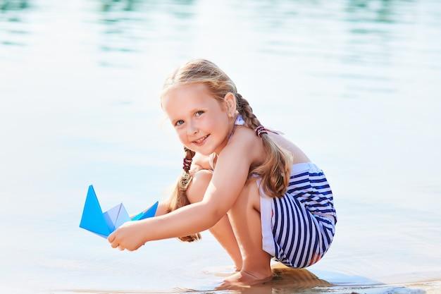 Schattig klein meisje origami boot buiten houden