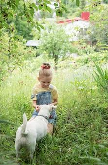 Schattig klein meisje plukt een kers van een boom in de kersentuin