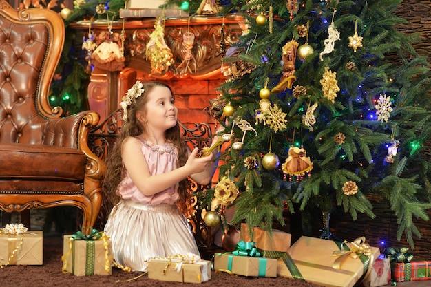 Schattig klein meisje poseren in de buurt van versierde kerstboom