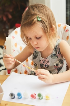 Schattig klein meisje schilderen in de kamer. idee voor doe-het-zelf binnenactiviteiten voor kinderen
