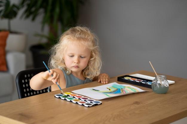 Schattig klein meisje schilderen op papier thuis