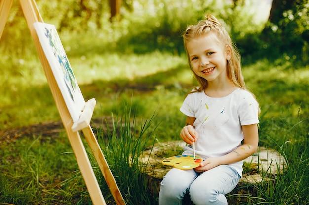 Schattig klein meisje schilderij in een park